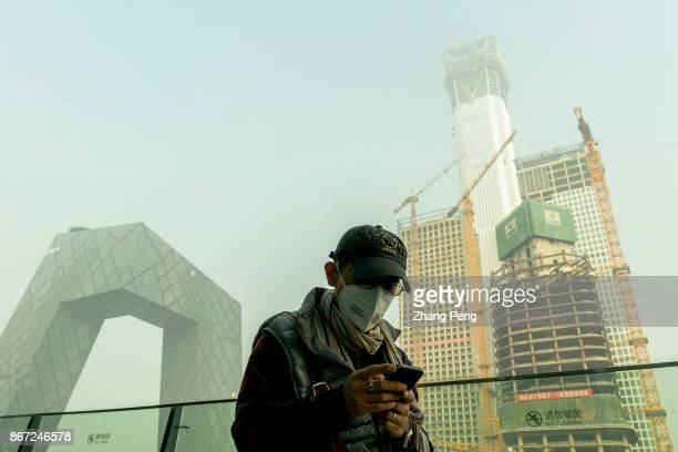 Man wearing mask walks in heavy haze at Beijing CBD. A severe air pollution attacks Beijing after the 19th National Congress of CPC.