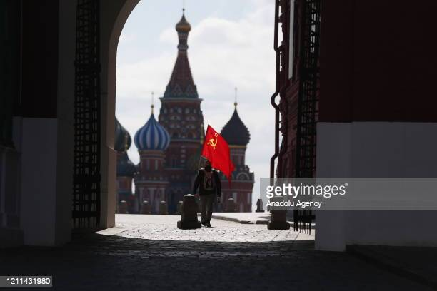 A man wearing mask walks with flag of Russian Communist Party at empty Red Square due to coronavirus pandemic on International Workers' Day in Moscow...