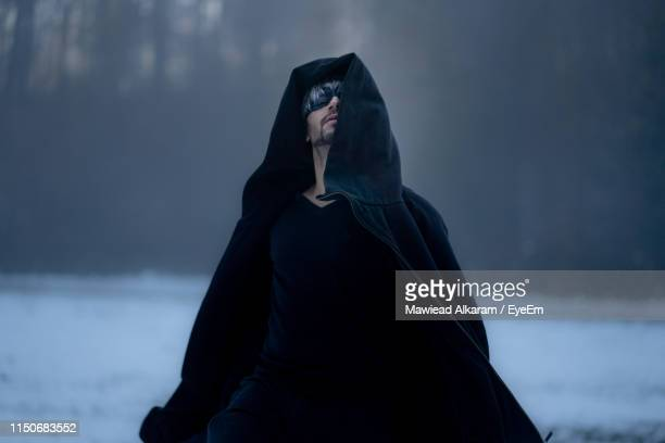 man wearing mask while standing in snow against trees - ケープ ストックフォトと画像
