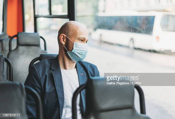 man wearing mask while traveling in bus - obscured face stock pictures, royalty-free photos & images