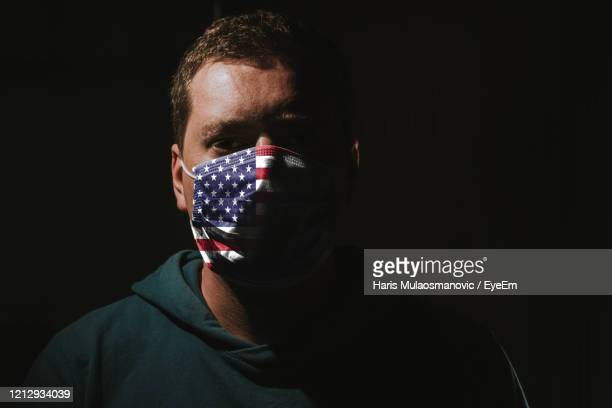 man wearing mask with american flag for protection of corona virus covid-19 sars-cov-2 - usa stock pictures, royalty-free photos & images