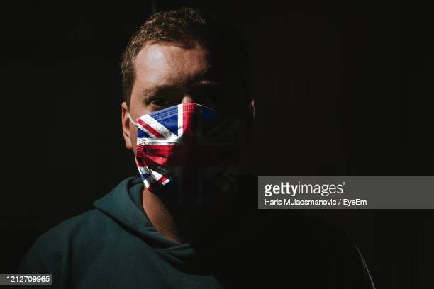 man wearing mask with united kingdom flag for protection of corona virus covid-19 sars-cov-2 - union jack stock pictures, royalty-free photos & images