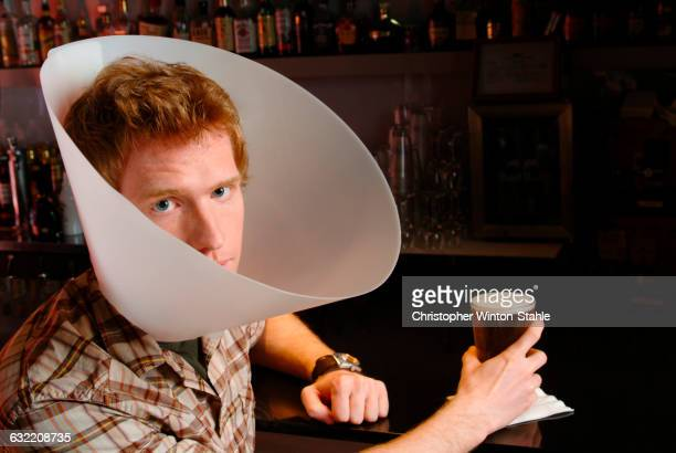 Man wearing medical cone in bar