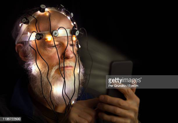 man wearing medical equipment while using mobile phone against black background - eeg stock pictures, royalty-free photos & images