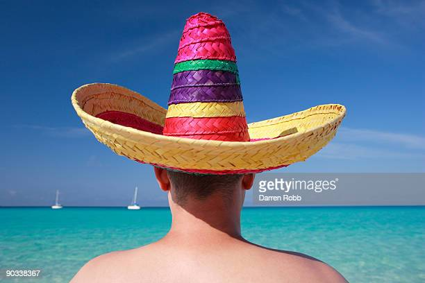 man wearing mexican sombrero on tropical beach - mexican hat stock pictures, royalty-free photos & images