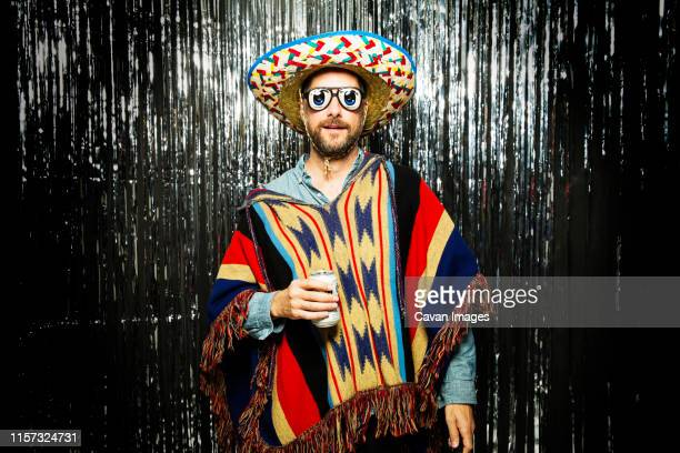 man wearing mexican themed party costume and funny glasses - cinco de mayo stock pictures, royalty-free photos & images