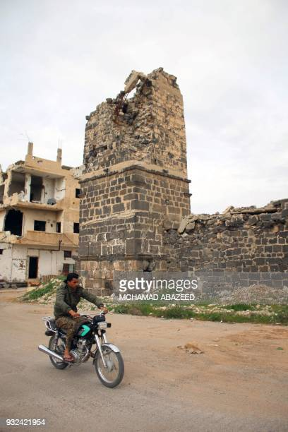 A man wearing military fatigue rides his motorcycle past Daraa's Omari mosque on March 15 2018 / AFP PHOTO / Mohamad ABAZEED