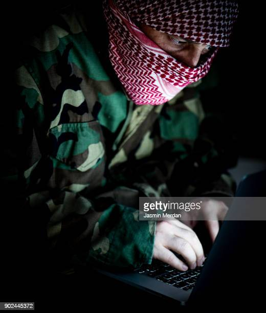 man wearing military uniform and kaffiyeh hiding face using laptop ready for cyber attack - military attack stock pictures, royalty-free photos & images