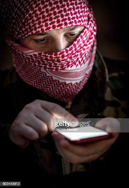 man wearing military uniform and kaffiyeh use no smartphone ready for cyber attack - military attack stock pictures, royalty-free photos & images