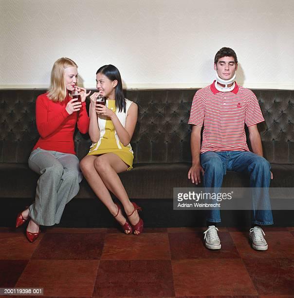 Man wearing neck brace sitting on bench beside two women drinking