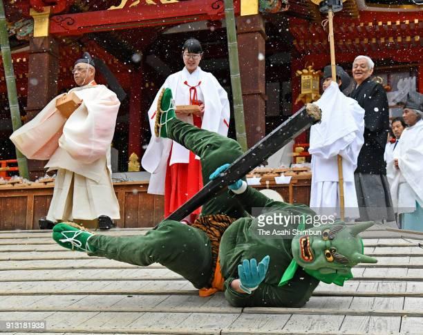 A man wearing ogre mask falls the slope as he is thrown beans during the Oniyarai ritual socalled beanscattering at Iwashimizu Hachimangu Shrine...