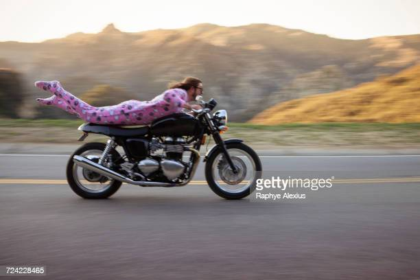 Man wearing onesie lying on front riding motorcycle, Malibu Canyon, California, USA