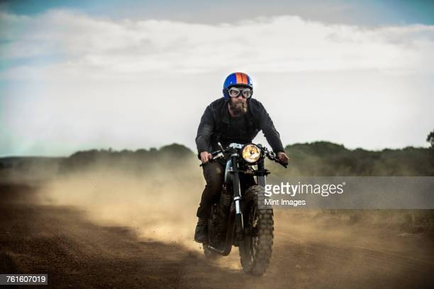 Man wearing open face crash helmet and goggles riding cafe racer motorcycle on a dusty dirt road.