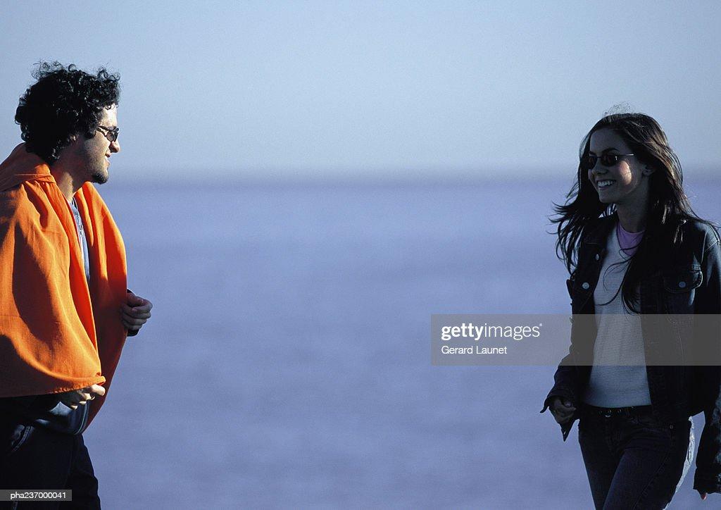 Man wearing orange blanket looking at woman near water. : Stockfoto