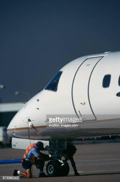 man wearing orange highviz tabard unhooking the towbar from a Continental Express Embraer ERJ145 after pushback