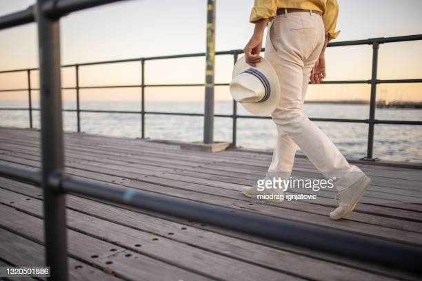 man wearing pants and espadrilles walking on wooden dock by sea - beige shoe stock pictures, royalty-free photos & images