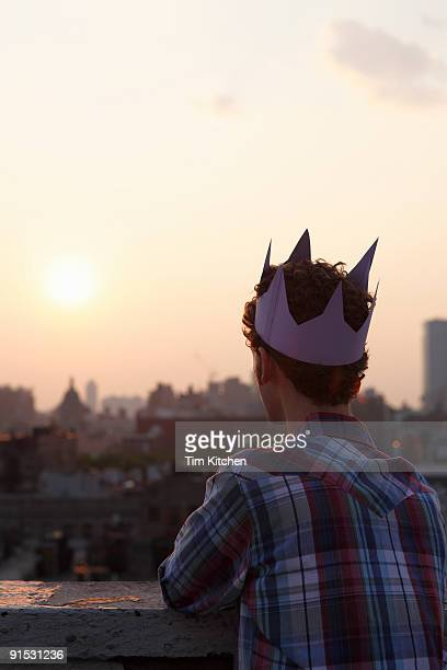 Man wearing paper crown looking over city, at dusk