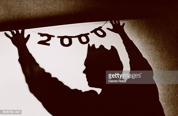 man wearing party hat, putting up year 2000 decoration (toned b&w) - 2000 stock pictures, royalty-free photos & images