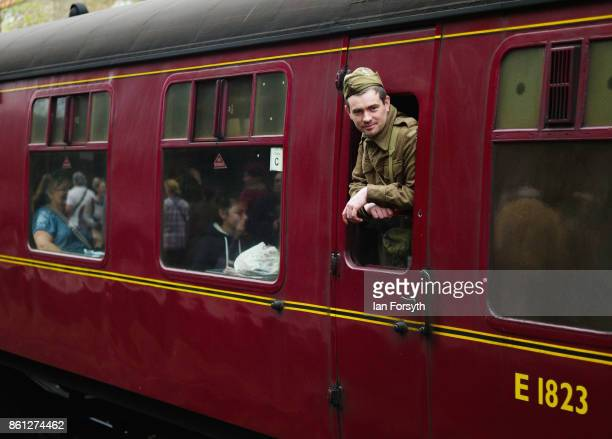 A man wearing period military uniform looks from the window of a steam locomotive carriage during the North Yorkshire Moors Railway 1940's Wartime...