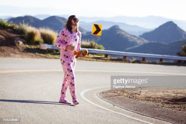 Man wearing pink onesie walking in road carrying teddybear, Malibu Canyon, California, USA