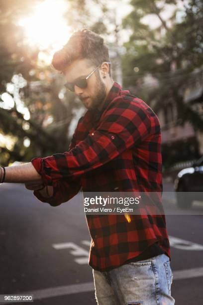 man wearing plaid shirt and sunglasses while standing on road - karohemd stock-fotos und bilder