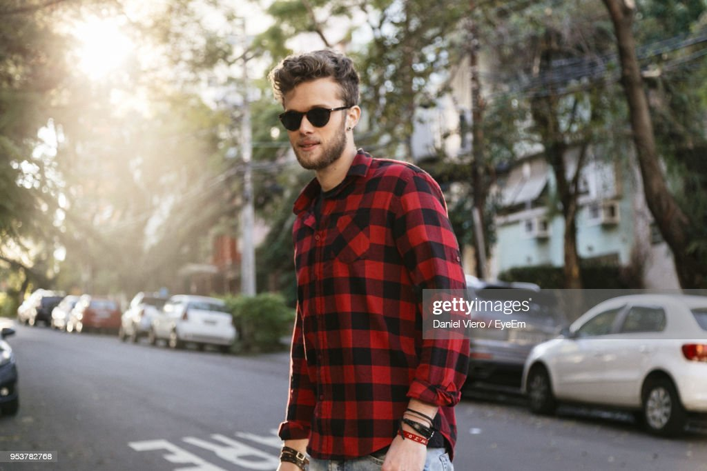 Man Wearing Plaid Shirt And Sunglasses While Walking On Road : Stock Photo