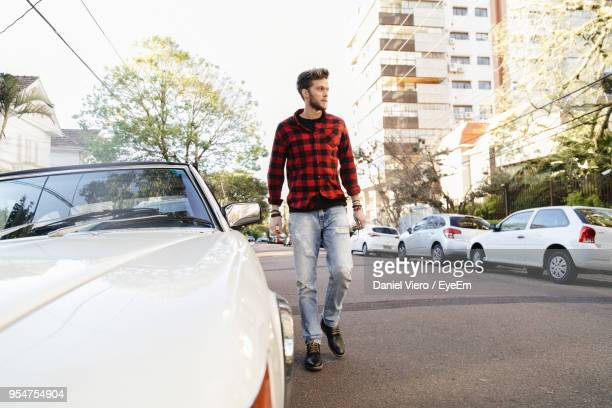 man wearing plaid shirt while walking on road - vêtement de peau photos et images de collection