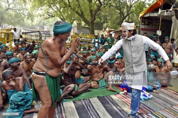 A man wearing PM Modi's mask beats a Tamil Nadu farmer during a play as part of protest seeking compensation for drought in the state at Jantar...