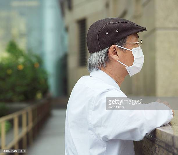Man wearing pollution mask, leaning on wall, side view