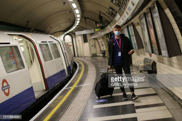 A man wearing PPE including a face mask as a precautionary measure against COVID19 leaves a London Underground Tube train in the evening rush hour at...