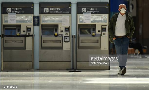 Man wearing PPE , including a face mask as a precautionary measure against COVID-19, walks past ticket machines at Waterloo Train station in central...