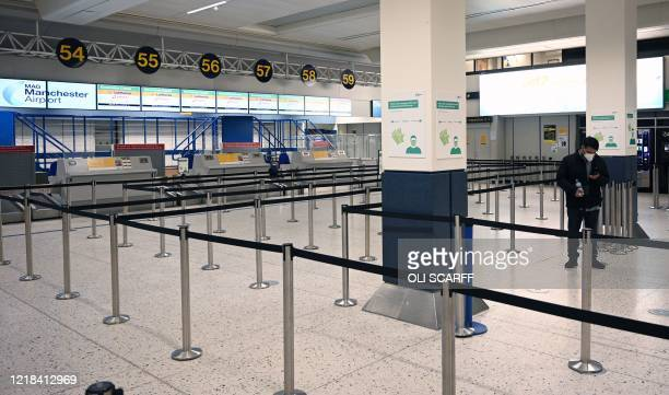 Man wearing PPE , including a face mask as a precautionary measure against COVID-19, stands at an empty check-in desk at Manchester Airport in...