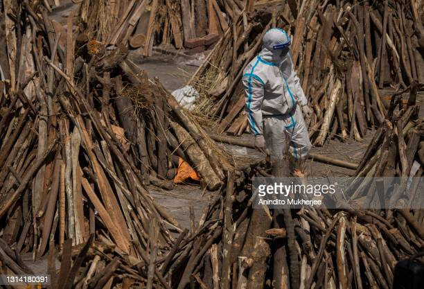 Man wearing PPE kit can be seen amid funeral pyres before they were lit to perform the last rites of the patients who died of the Coronavirus disease...