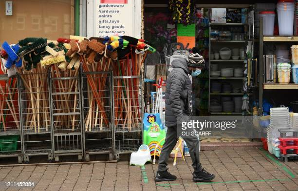 Man wearing PPE , of a face mask as a precautionary measure against COVID-19 walks past a hardware store in Oldham, north west England, on May 1 as...
