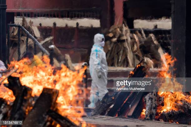 Man wearing PPE performs the last rites to his relative who died of the Covid-19 coronavirus disease at a crematorium on April 20, 2021 in New Delhi,...