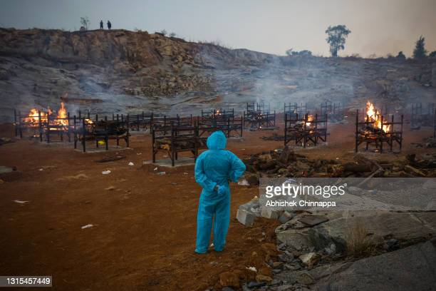 Man wearing PPE watches mass cremations in a disused granite quarry repurposed to cremate the dead due to COVID-19 on April 30, 2021 in Bengaluru,...