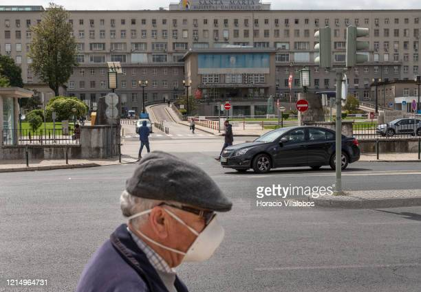 A man wearing protective a mask walks by Santa Maria Hospital where a number patients infected with COVID19 Coronavirus are under treatment on March...