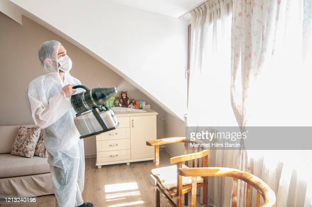 man wearing protective biological suit and gas-mask due to mers coronavirus global pandemic warning and danger - disinfection stock pictures, royalty-free photos & images