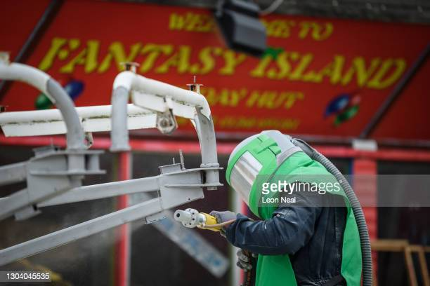 Man wearing protective clothing and breathing apparatus removes the paint from a fairground ride during renovation work at the Fantasy Island fun...