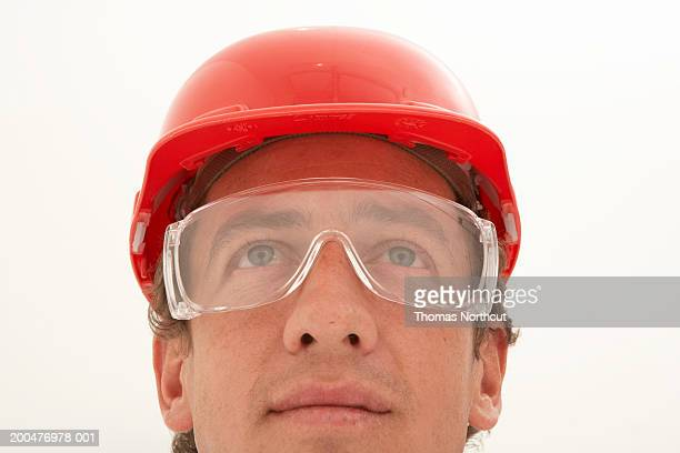 Man wearing protective eyewear and hard hat, looking up