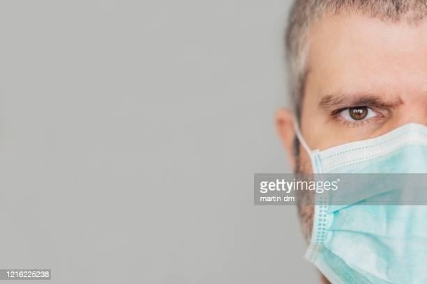 mann trägt schutzbeschützende gesichtsmaske während covid-19-pandemie - atemschutzmaske stock-fotos und bilder