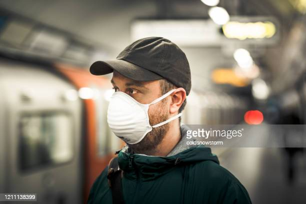 man wearing protective face mask in city subway station - train vehicle stock pictures, royalty-free photos & images