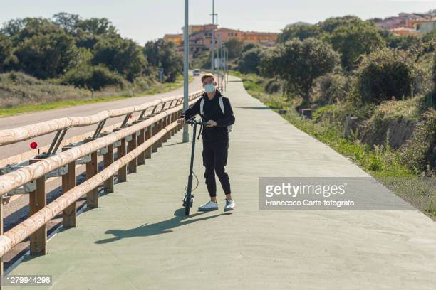 man wearing protective face mask riding electric scooter - tempio pausania stock pictures, royalty-free photos & images