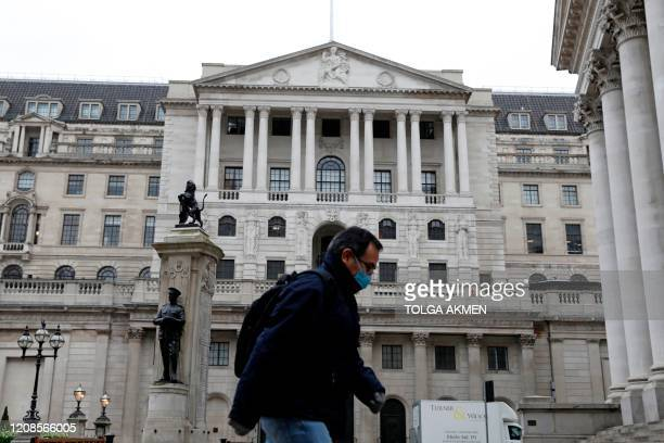 A man wearing protective face mask walks past the Bank of England in the City of London on March 30 as life in Britain continues during the...