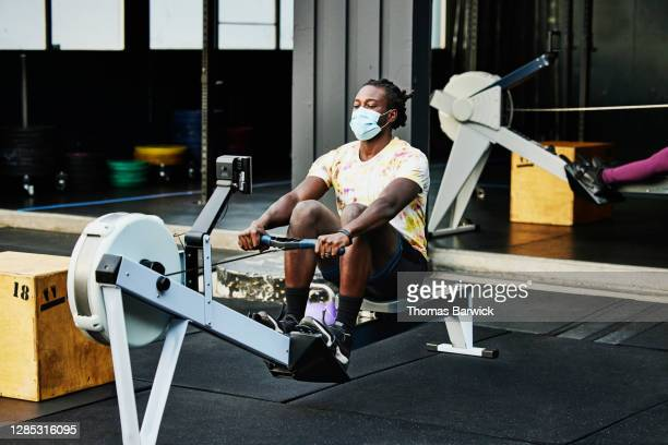man wearing protective face mask working out on rowing machine at outdoor gym - gym stock pictures, royalty-free photos & images