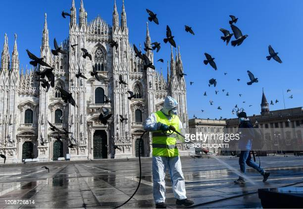 Man wearing protective gear, working for environmental services company AMSA, sprays disinfectant on Piazza Duomo in Milan, on March 31, 2020 during...