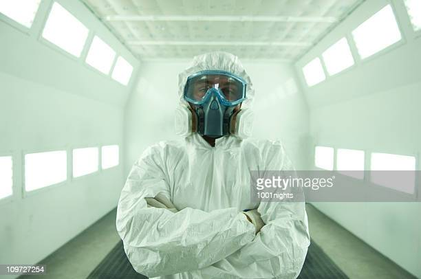 Man Wearing Protective Mask and Suit in Automotive Painting Chamber