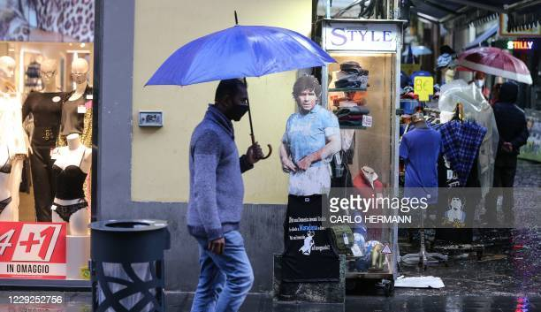 Man, wearing protective mask, holds an umbrella as he passes ahead of a picture of Diego Maradona in central Naples, on October 2020. - Italy's...