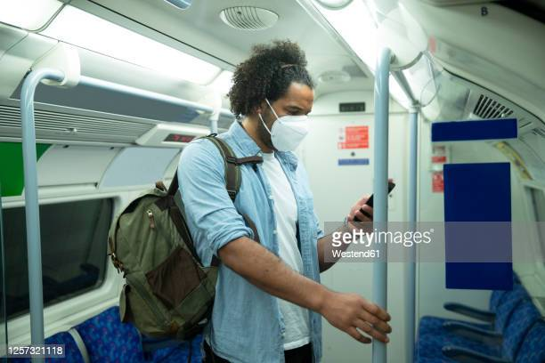 man wearing protective mask standing in underground train looking at cell phone, london, uk - vertical red tube fotografías e imágenes de stock