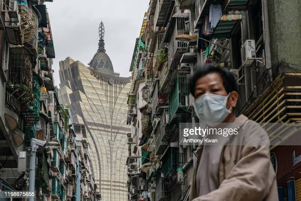 A man wearing protective mask walks across a street in front of the Grand Lisboa Hotel in a residential district on February 5 2020 in Macau China...